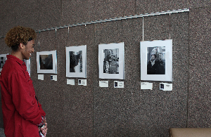 photo: a high school aged boy looks at photographs framed on the wall of the Ohio Civil Rights Commissions' office